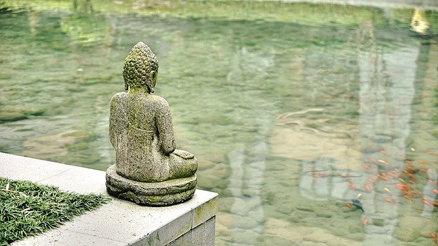 A statue of a person sitting on a rock