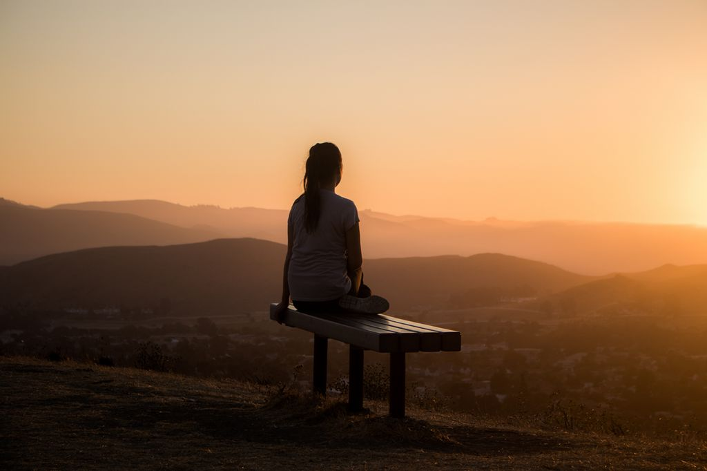 A man sitting on a bench in front of a sunset