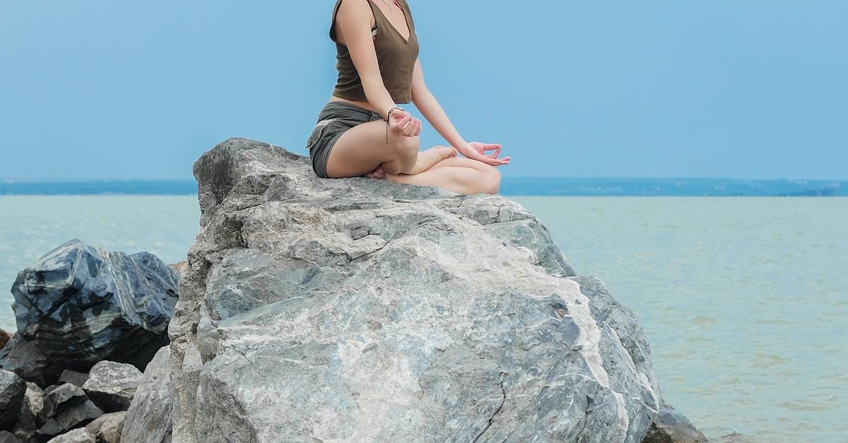 A woman sitting on a rock near the ocean